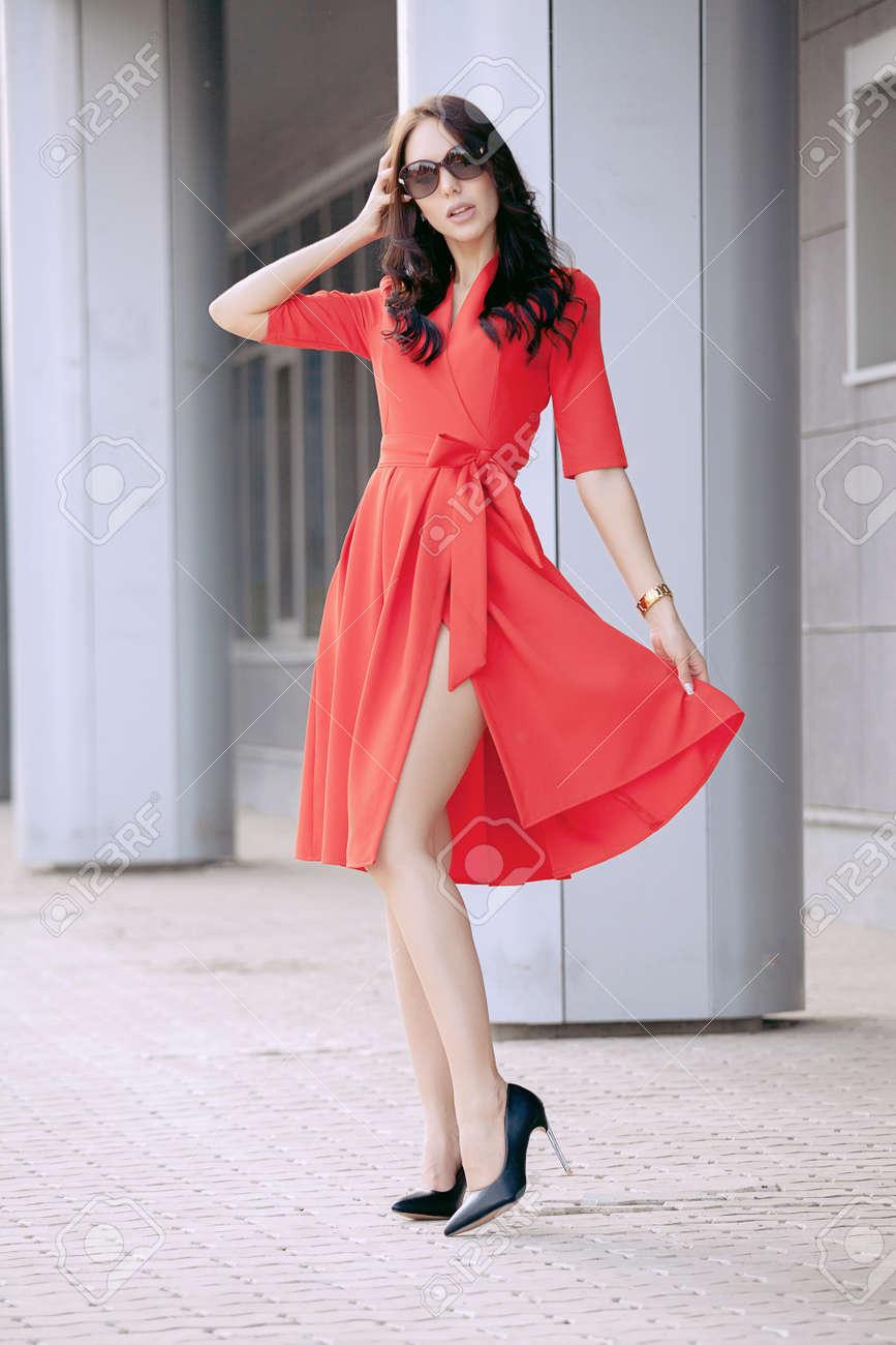 Hermosa Morena Joven Con Un Vestido Rojo Zapatos Negros De Tacón Alto Lentes Oscuros Caminando Por La Calle Foto De Moda