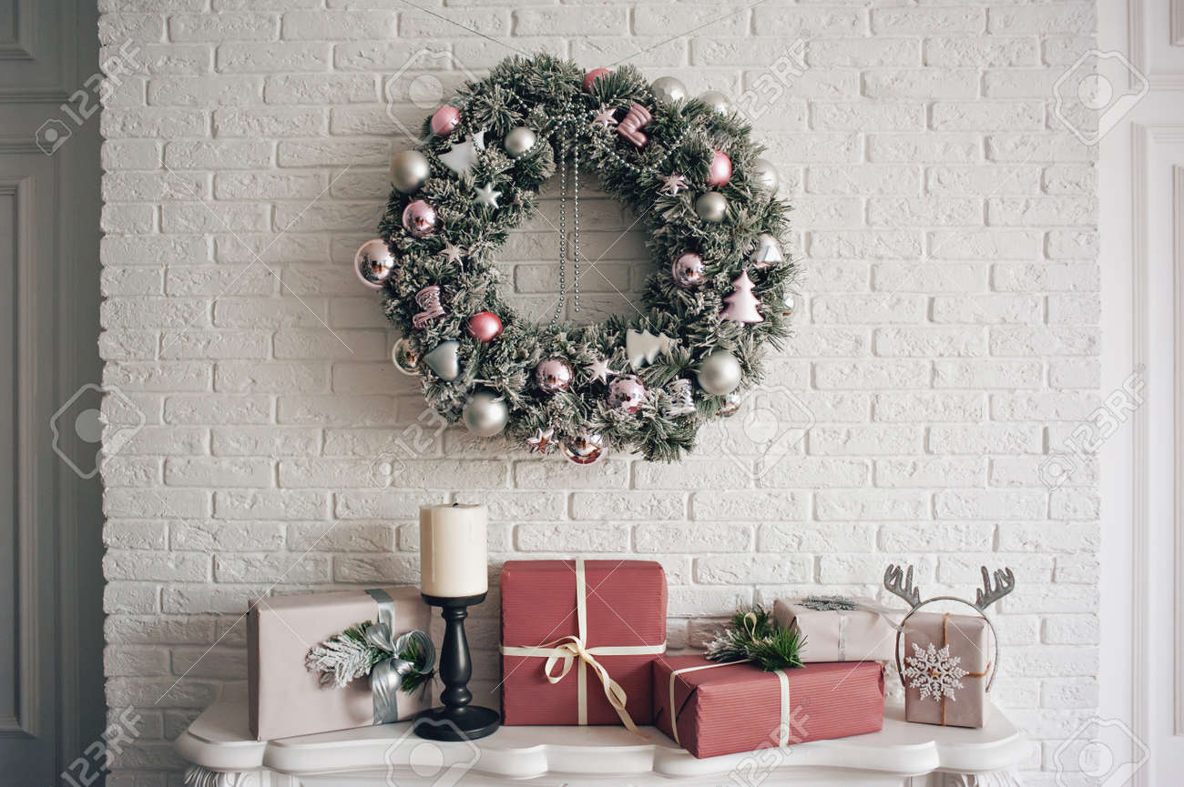 a traditional bright christmas wreath hanging over the fireplace on a white brick wall