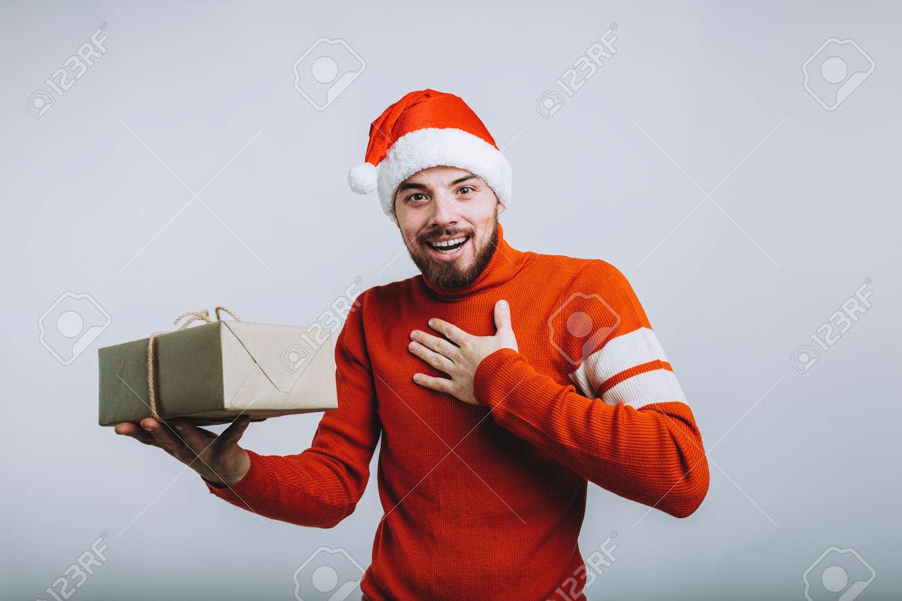 Gut Aussehender Mann In Sankt Hut, Der Ein Weihnachtsgeschenk Hält ...