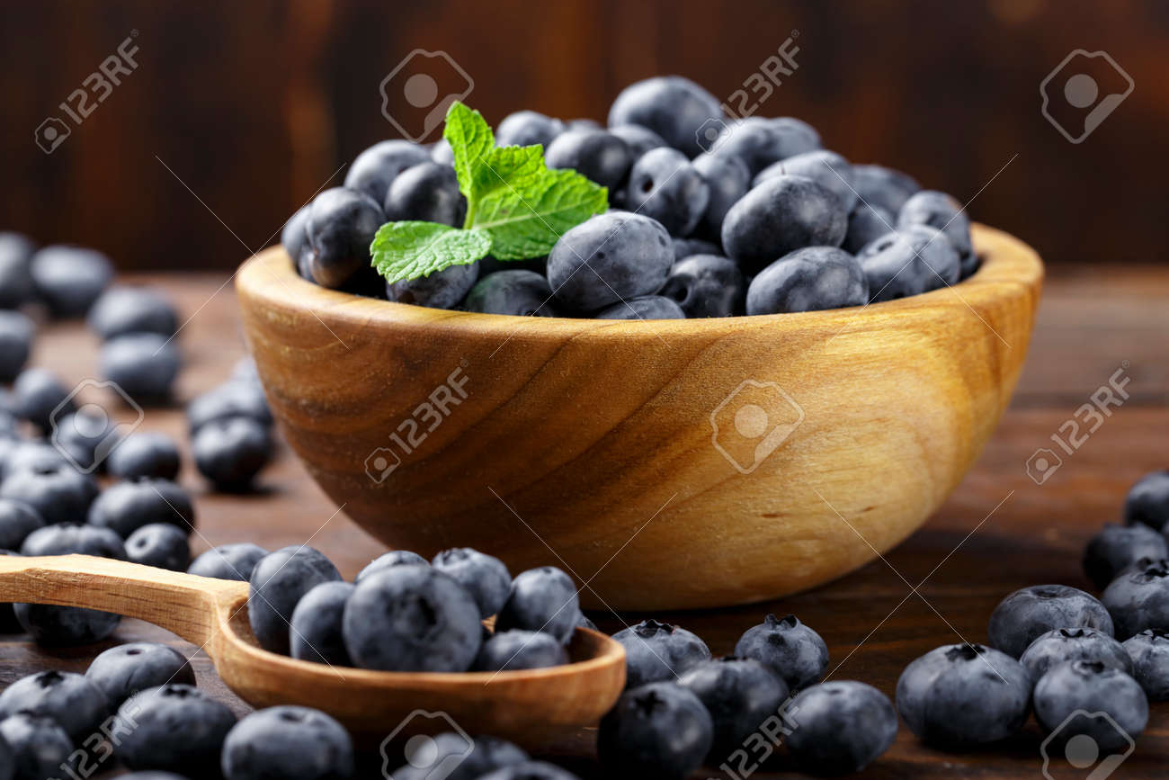 Freshly picked blueberries in wooden bowl on a wooden table. Healthy fruits. Blueberry antioxidant. - 151691003