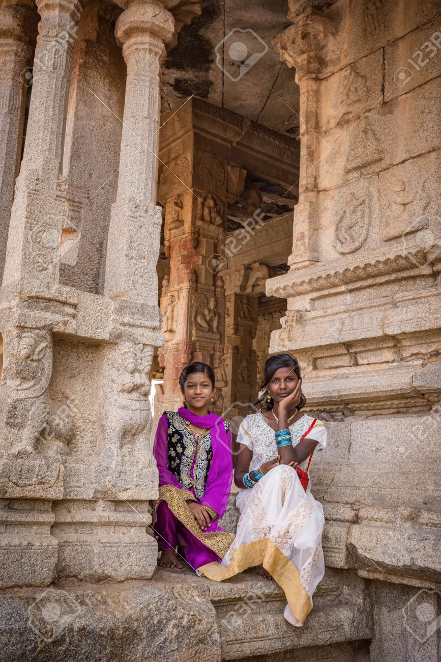Hampi, Karnataka, INDIA - JANUARY 16, 2018: Portrait of Indian girls dressed in national dresses. Girls are sitting at the entrance to the ancient temple. Group of Monuments at Hampi - 140995689