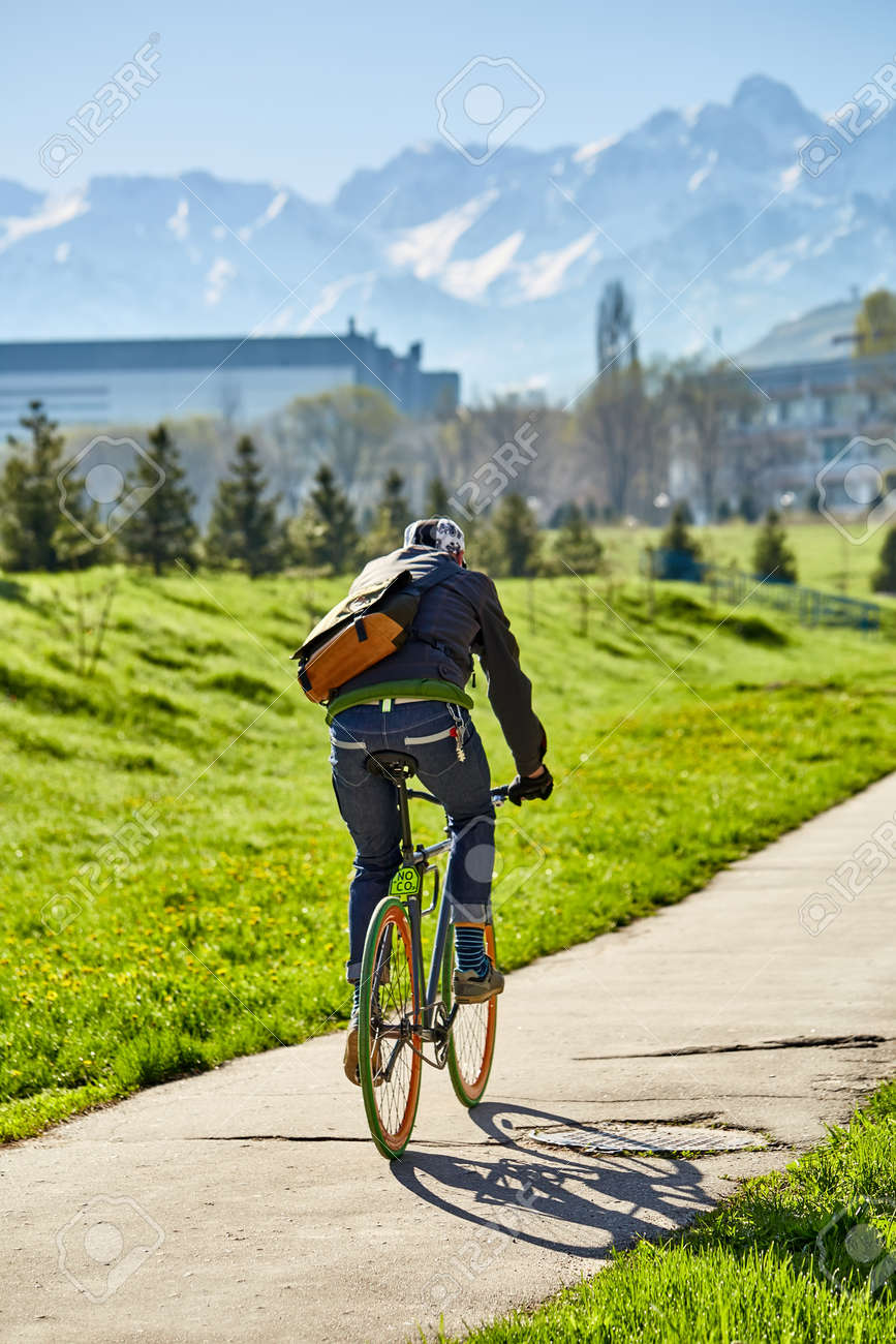 A cyclist rides on a road in the city against a background of green grass and mountains. city of Almaty. Ecological transport. - 136209313