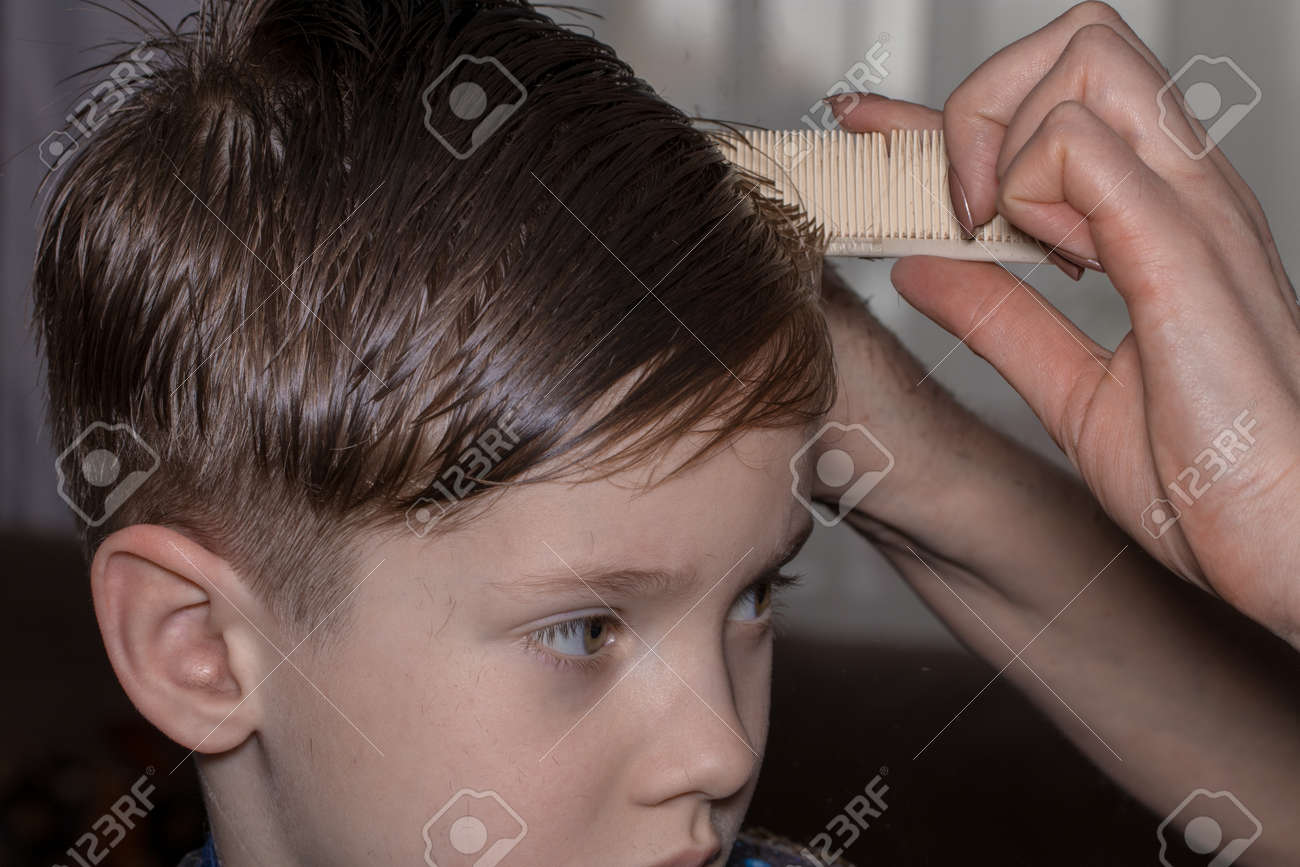 Side View Of Cute Little Boy Getting Haircut By Hairdresser At