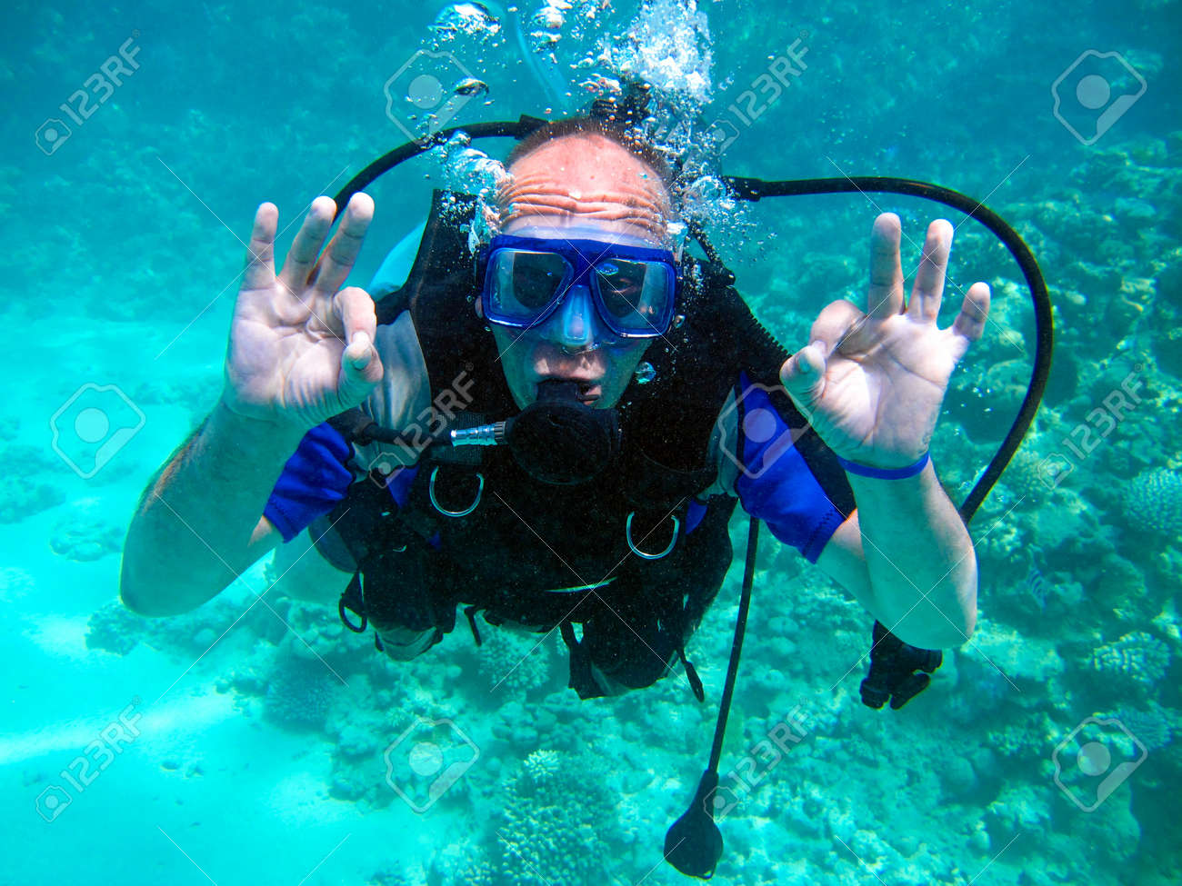 Man scuba diver and beautiful colorful coral reef underwater. - 134889560