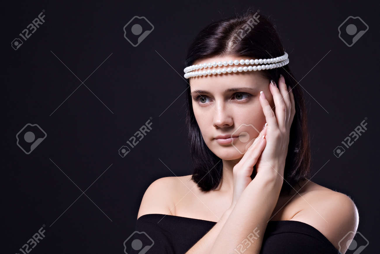 Beautiful Brunet Woman With A Pearl Necklace On Her Head On A Black  Background Stock Photo