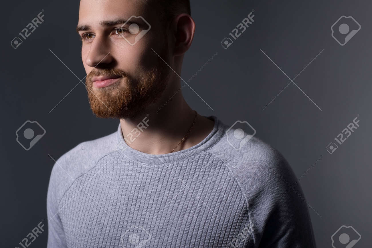 closeup, dramatic portrait of a handsome bearded guy of twenty-five years old, in a gray sweater, on a gray background. Casual style. Sweater, mens jacket. Smiling bearded young guy. Dark colored man portrait - 169874348