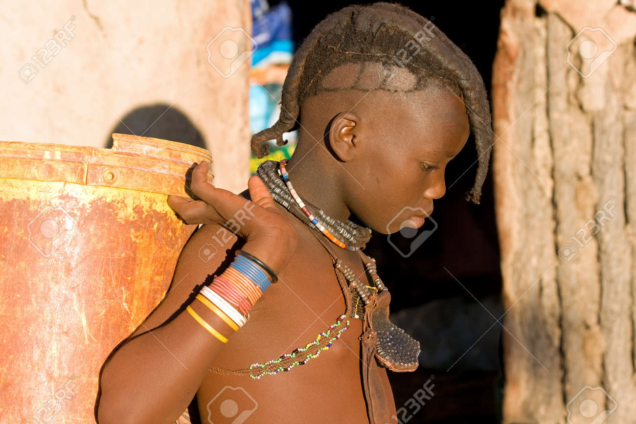Himba Boy With Traditional Hair Style And Jewelry Carrying A Stock
