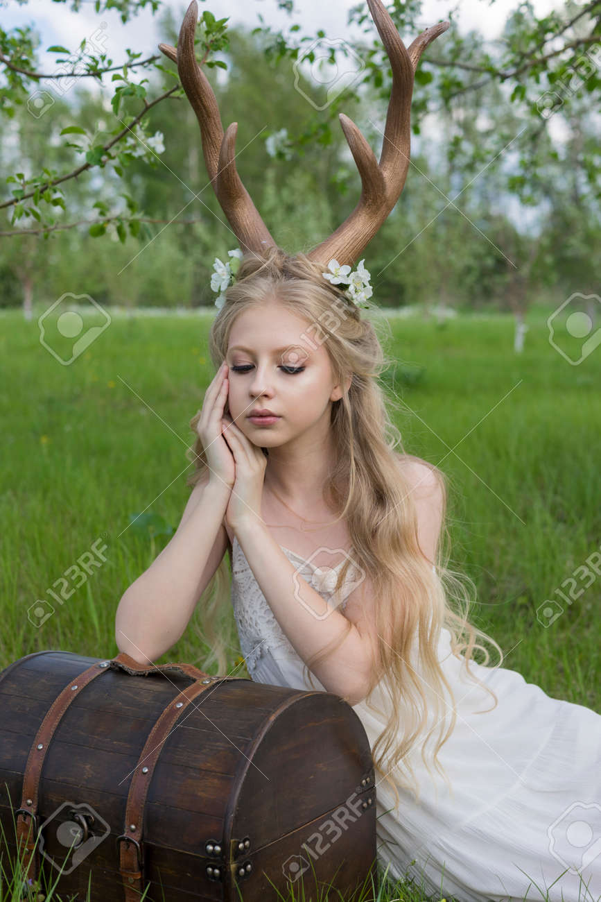 Teen Beautiful Blonde Girl Wearing White Dress With Deer Horns On