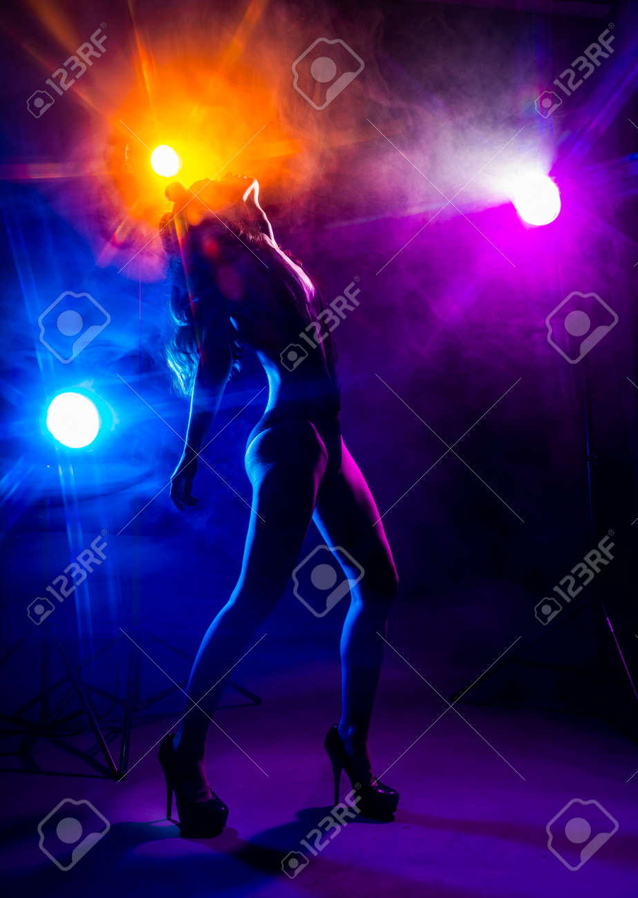 Beautiful slim dancer girl wearing lingerie and high heels posing in the rays of light in a colorful smoke. Artistic, conceptual, silhouette, commercial and advertising design. - 157845644