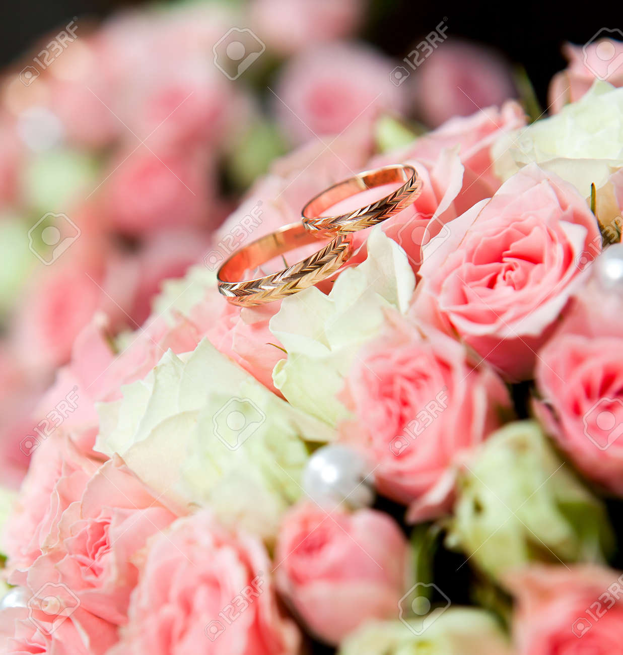 Gold wedding rings of the groom and the bride on a bunch of flowers. Stock Photo - 13905597