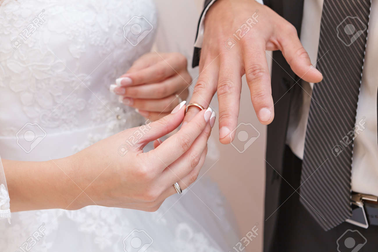 Hand Of The Groom And The Bride With Wedding Rings At A Wedding ...