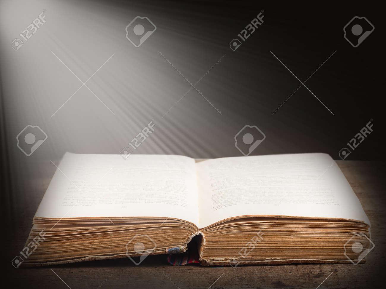 Ouvrir Le Livre Illumine Par Un Faisceau Lumineux De La Lumiere Sur Abstraite Fond Sombre