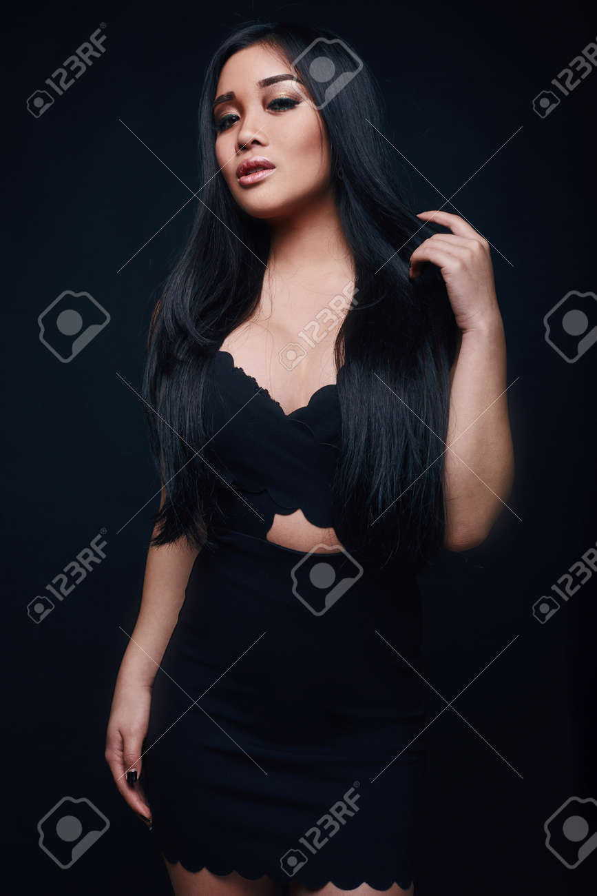 720740f17a17 Fashion swag portrait of beautiful elegant asian woman in formal dress on black  background Stock Photo