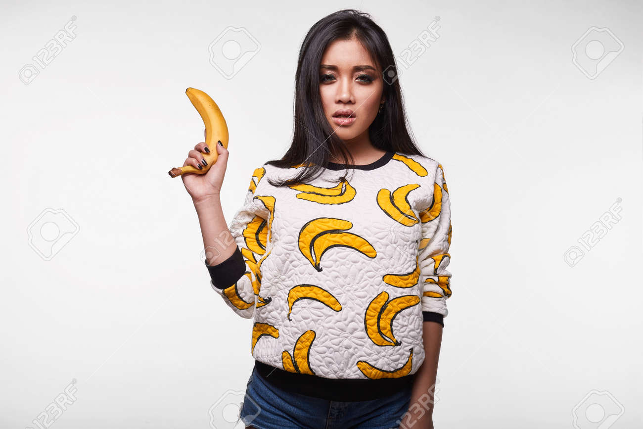 6b541b226cb Fashion swag portrait of beautiful elegant asian woman in funny banana t- shirt on white