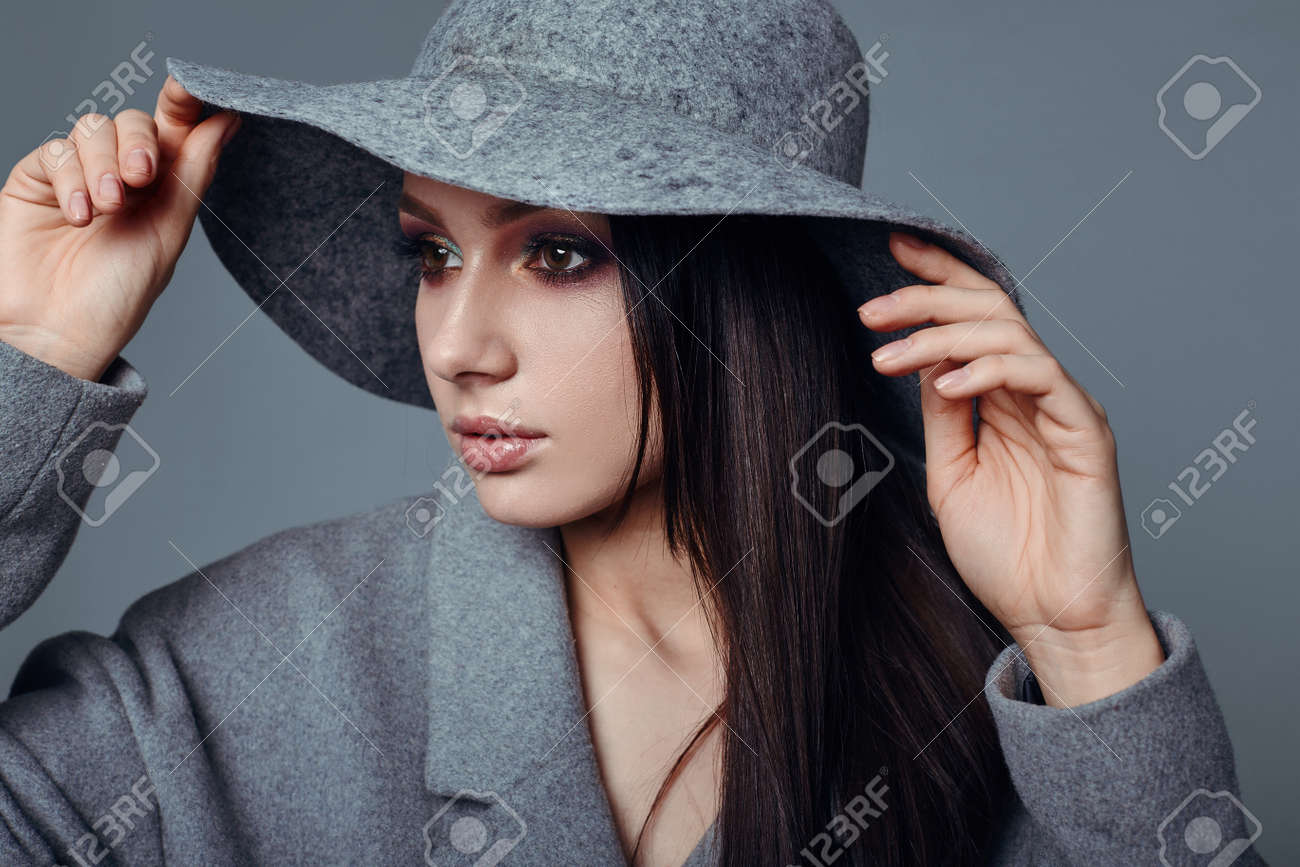 Stock Photo - young fashion brunette woman beauty portrait posing in studio wearing  in gray coat and hat f374a3a2acc7
