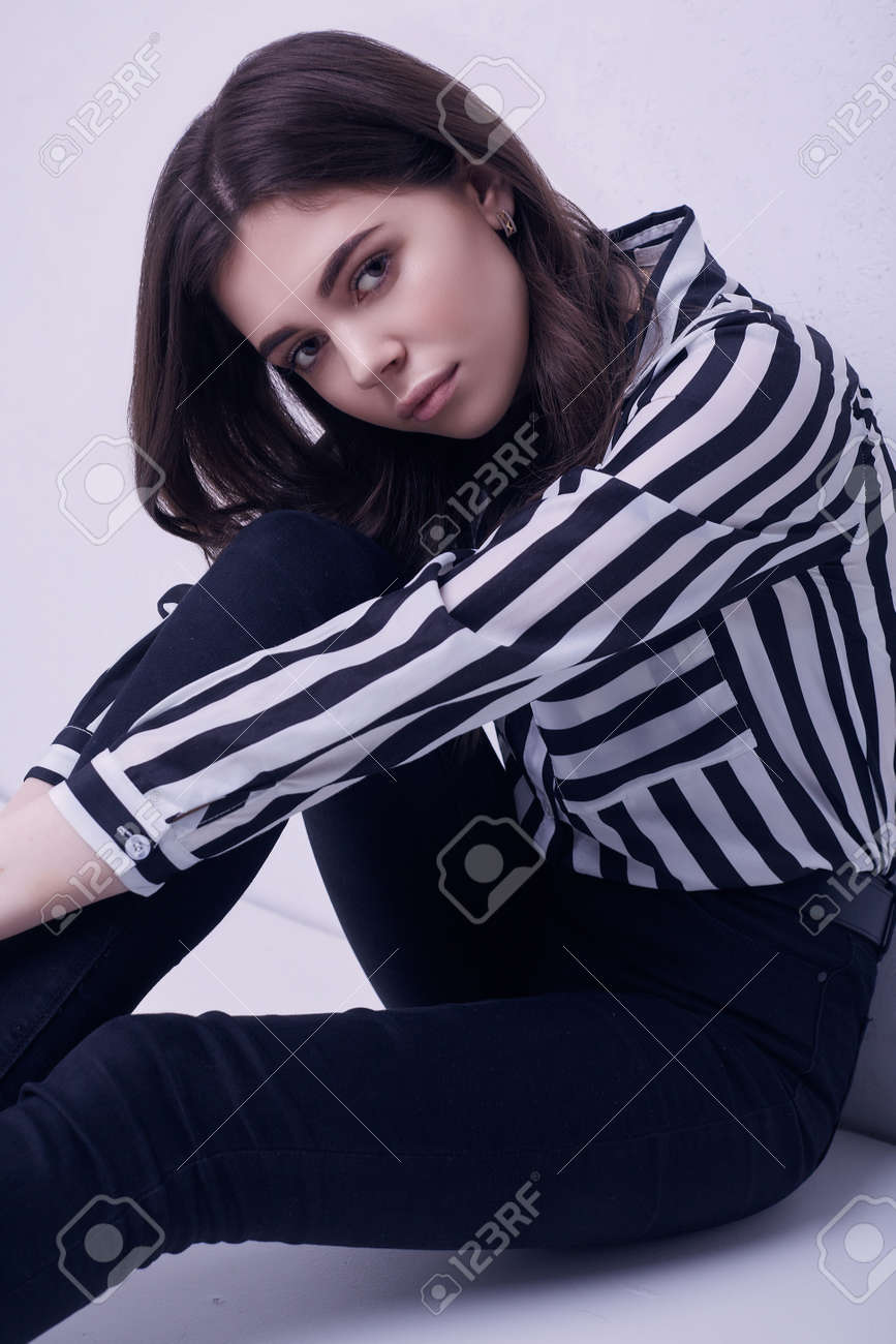 525ad0ff77 Portrait of fashion brunette woman wearing a striped blouse and jeans  isolated on white background in