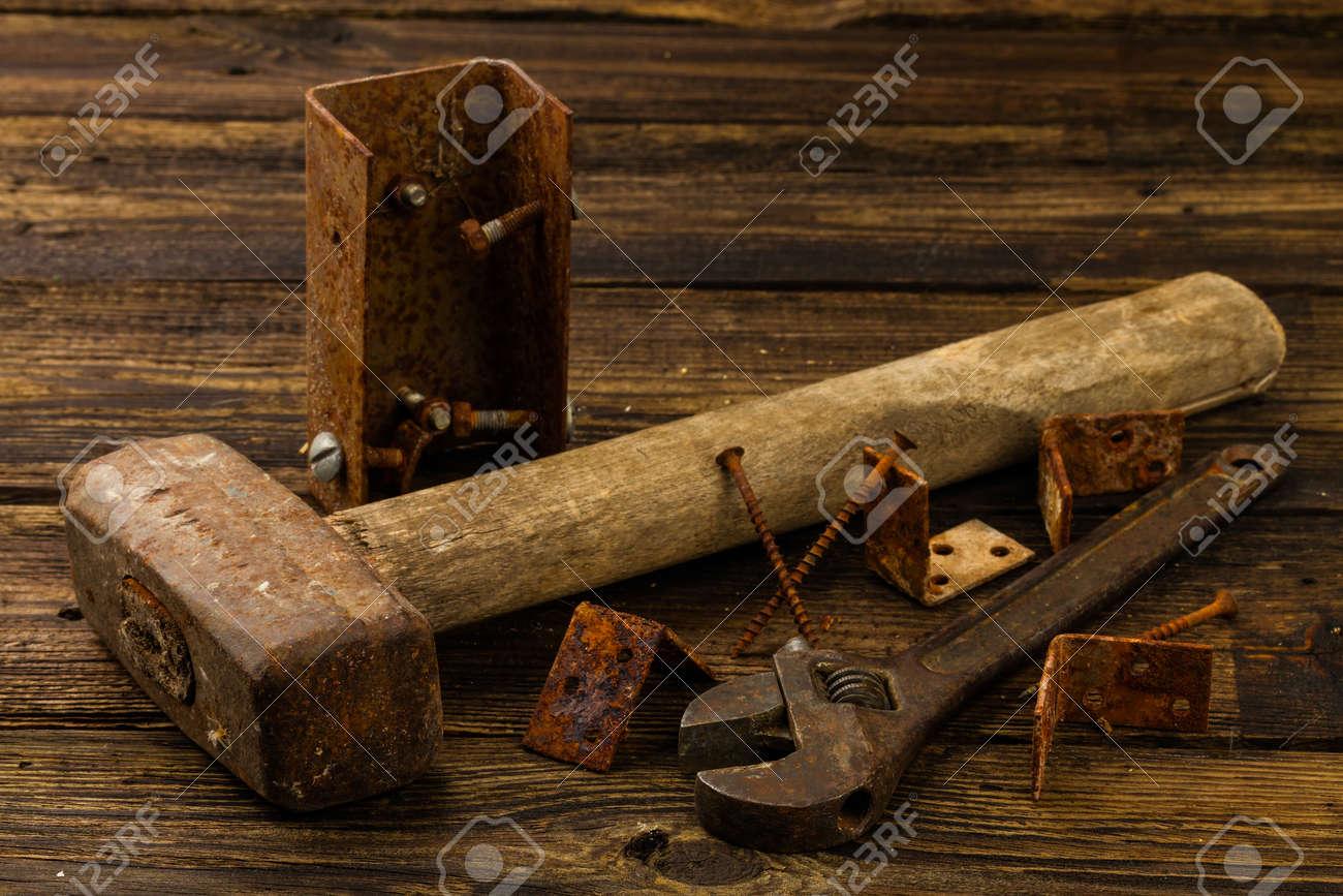 prezzi incredibili grandi affari immagini dettagliate Bretelle angolo, viti, cacciavite, martello e chiave inglese regolabile su  sfondo di legno