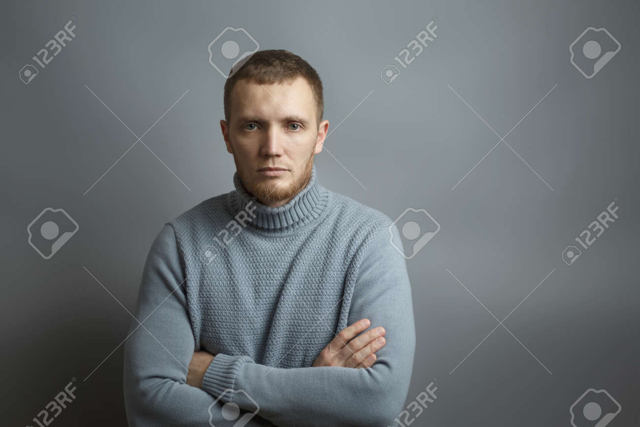 Man is seriously looking at the camera with his arms folded across his chest. On a gray background. Studio photo. - 141448322