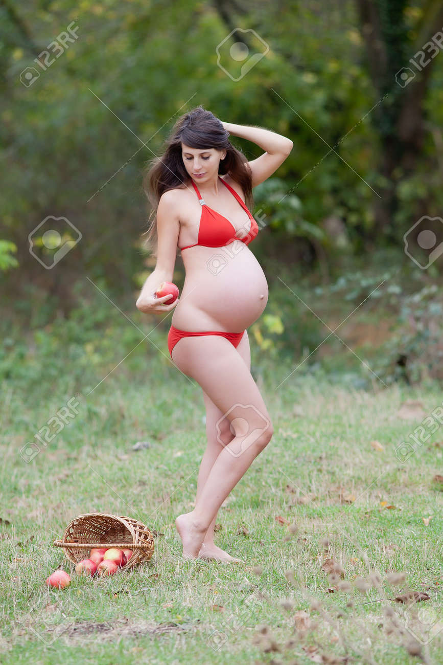 b6f2283b1 Pregnant woman in the autumn park. Expectant mother in red swimwear posing  on open air