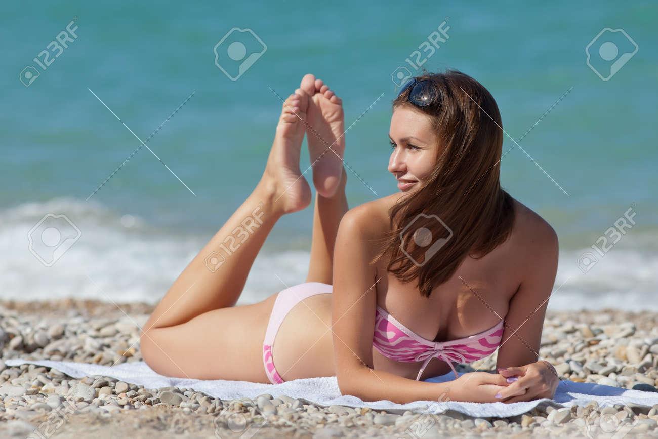 1111edfa2e44 La muchacha atractiva en traje de baño Acostado boca abajo en la arena  bronceado mujer joven