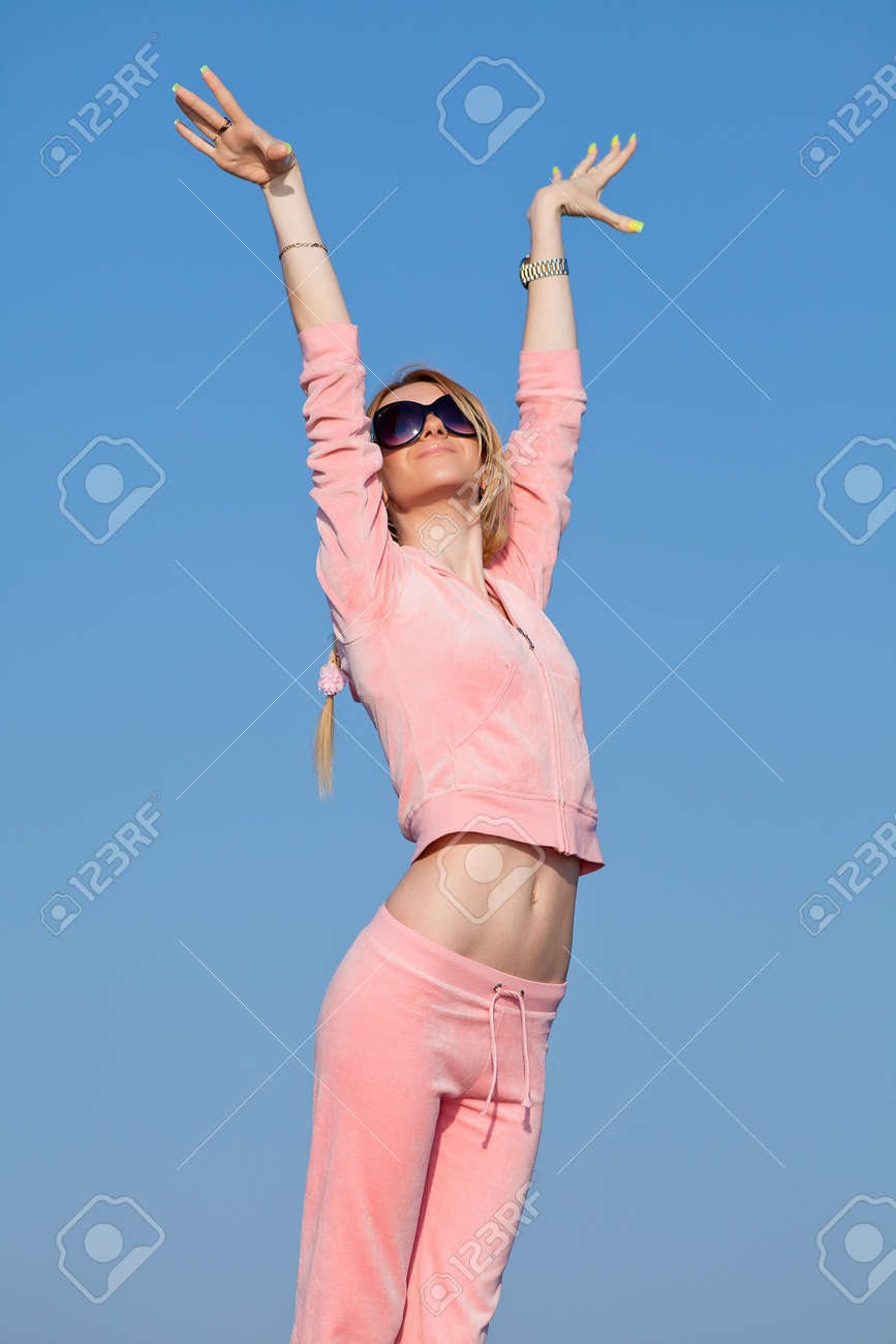 Attractive young woman in pink sportswear exercising against the sky   Girl in sunglasses outdoors Stock Photo - 14175562
