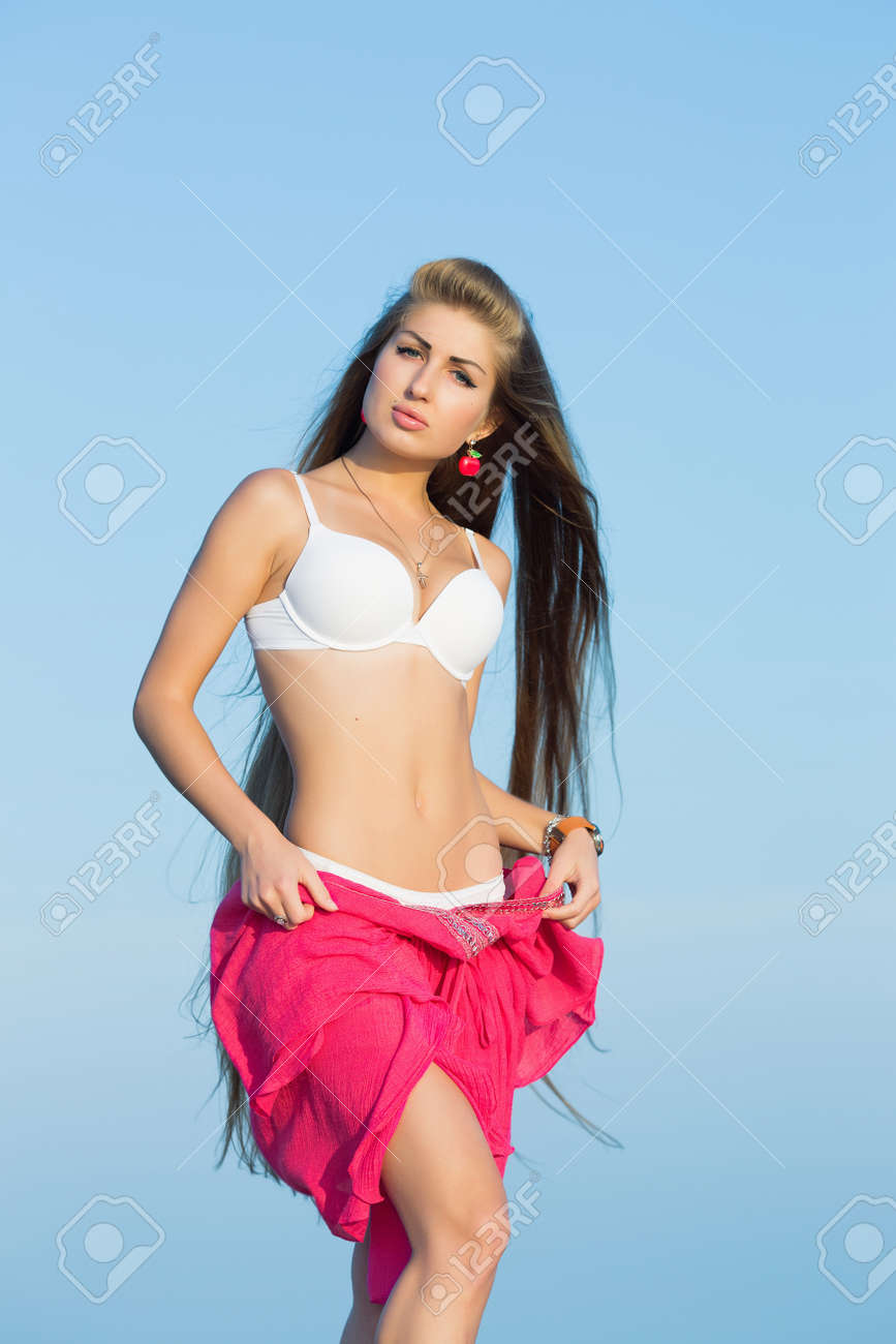 long-haired girl on the beach young woman undressing outdoors