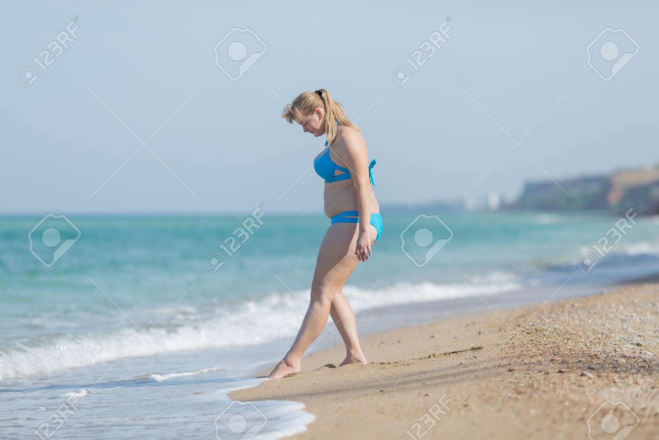 a6fdd28c5ad6 Mujer en traje de baño en la playa de arena. Mujer con sobrepeso en traje  de baño entrando en el mar