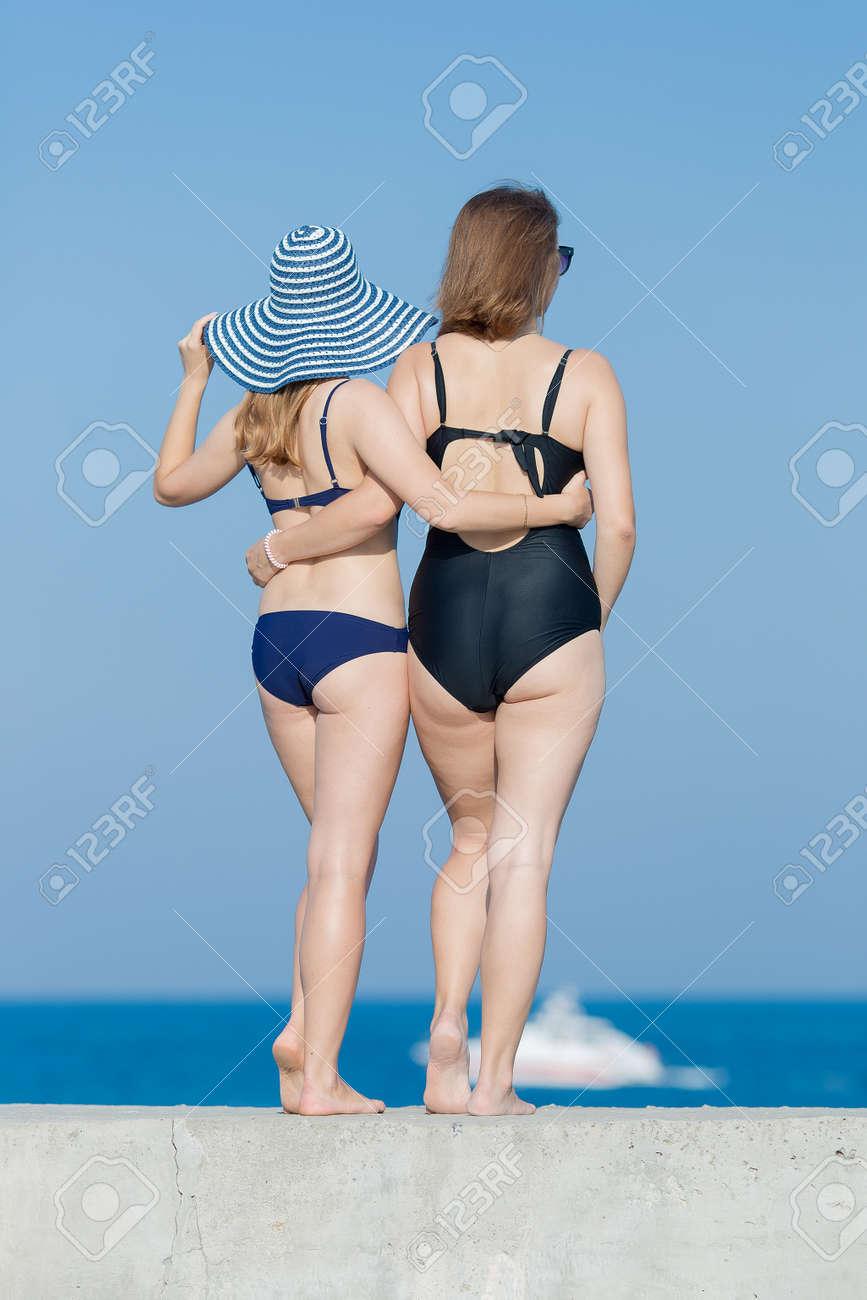 4e2a17a73ddb Dos mujeres jóvenes atractivas en trajes de baño contra el cielo, vista  posterior. Dos chicas rubias en traje de baño de una sola pieza posando al  ...