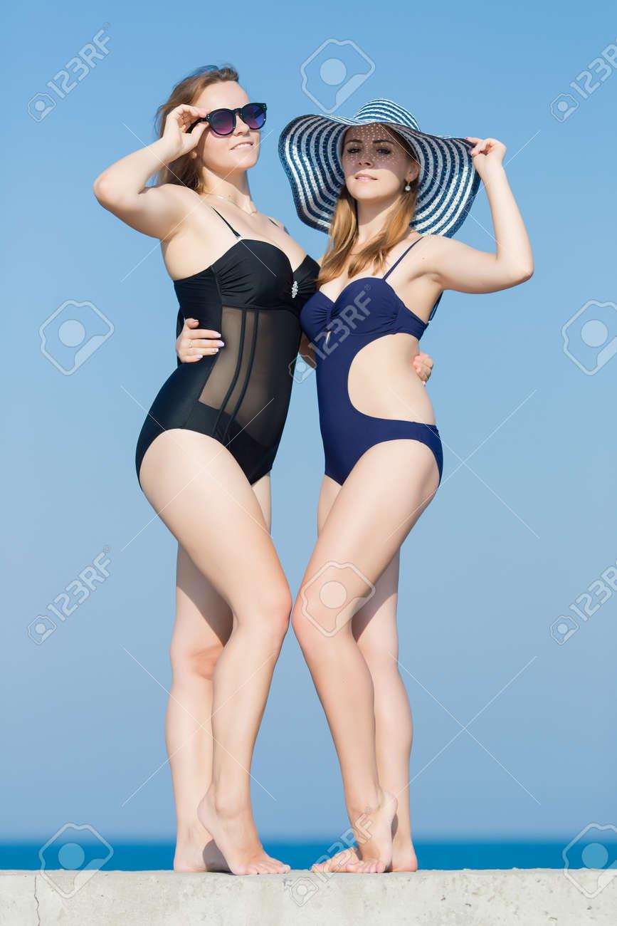 dfa9087f1d04 Dos mujeres jóvenes atractivas en trajes de baño contra el cielo. Dos  chicas rubias en traje de baño de una sola pieza posando en el aire abierto  ...