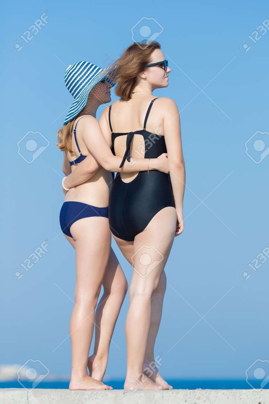 954285ebc590 Dos mujeres jóvenes atractivas en trajes de baño contra el cielo. Dos  chicas rubias en traje de baño de una sola pieza posando al aire libre  mirando a ...