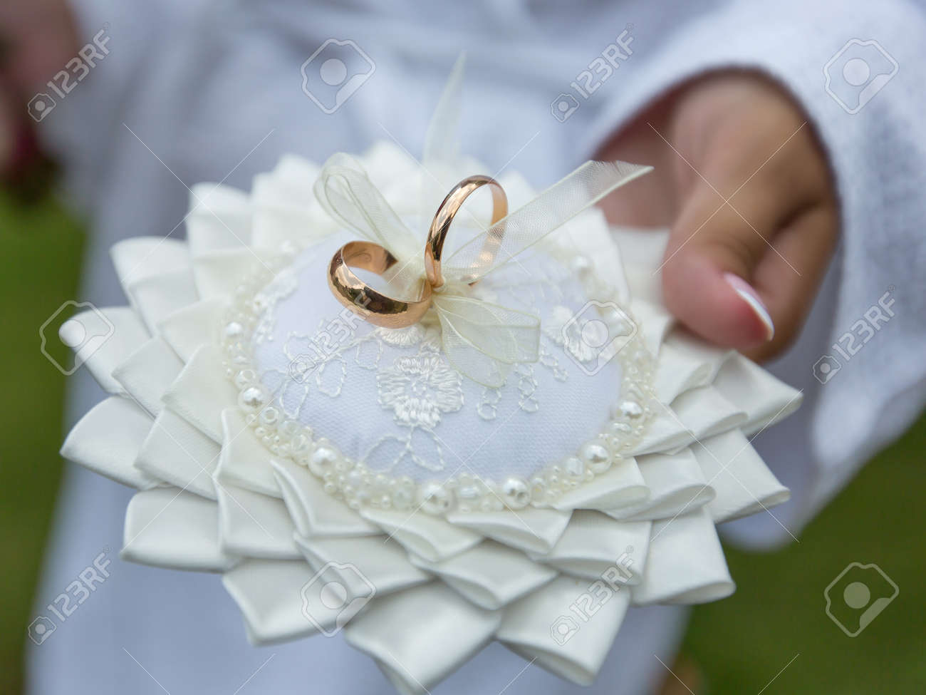Two Wedding Rings Attached To Pillow For Rings Bride Holds Ring