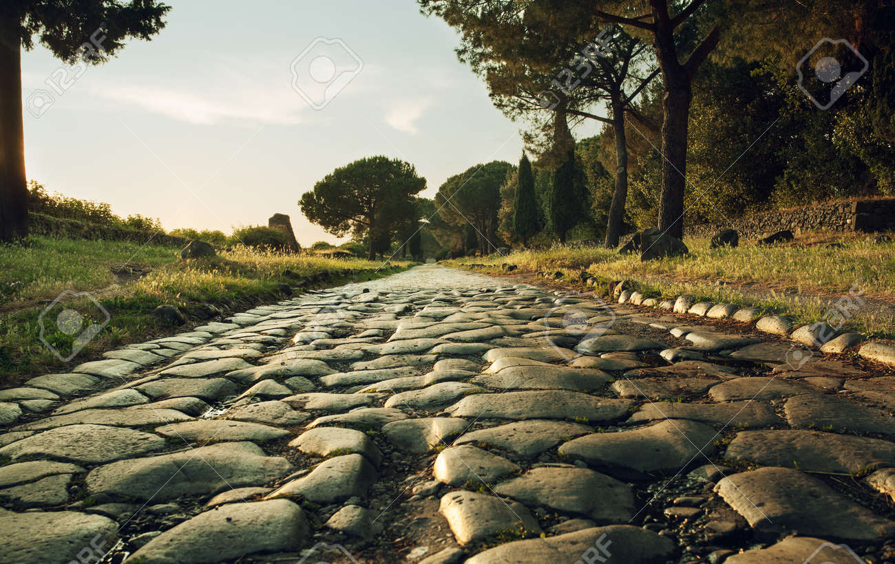 antique road via appia antica in rome italy on sunset stock photo