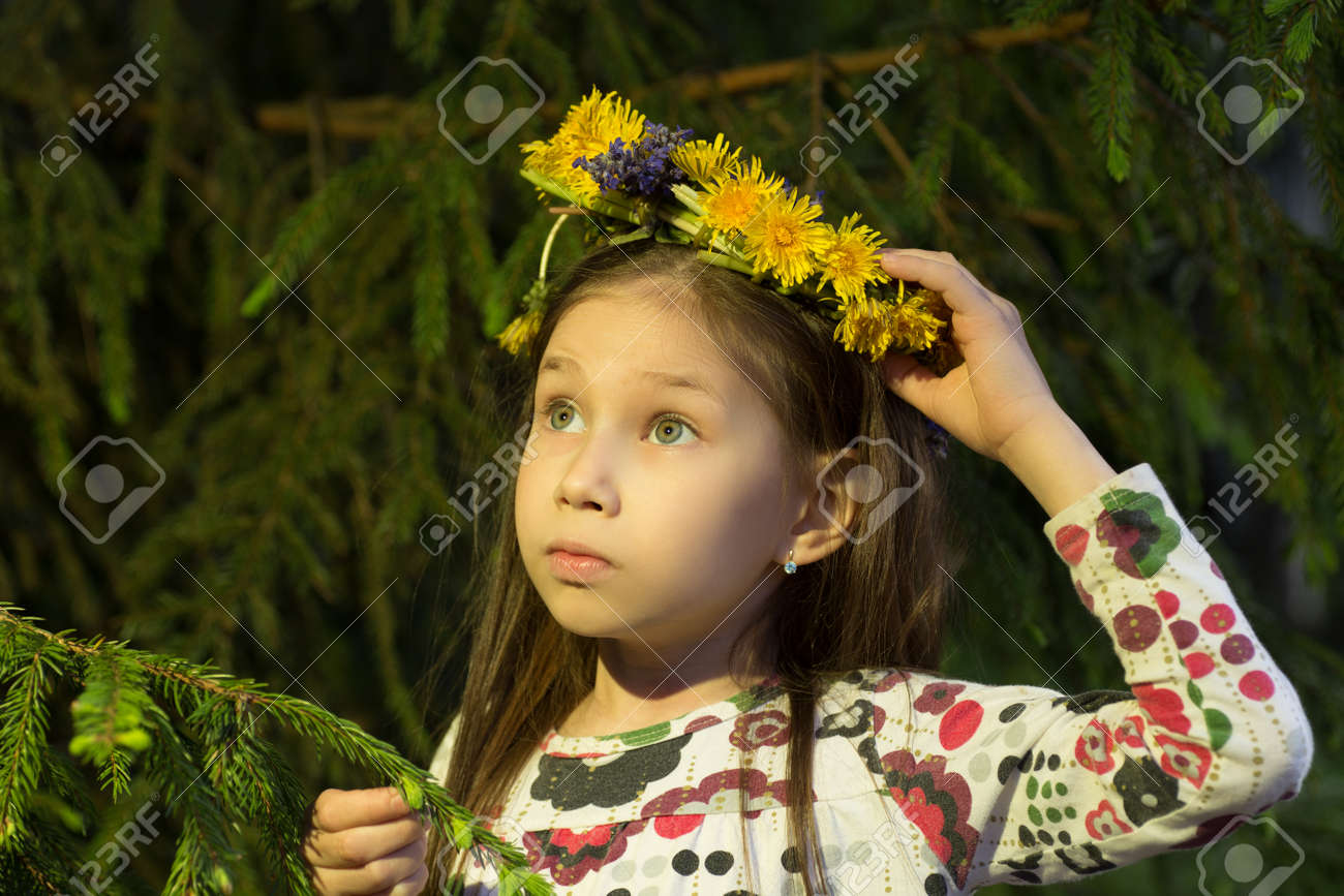 cute girl in flowers wreath is looking out of fir tree in forest