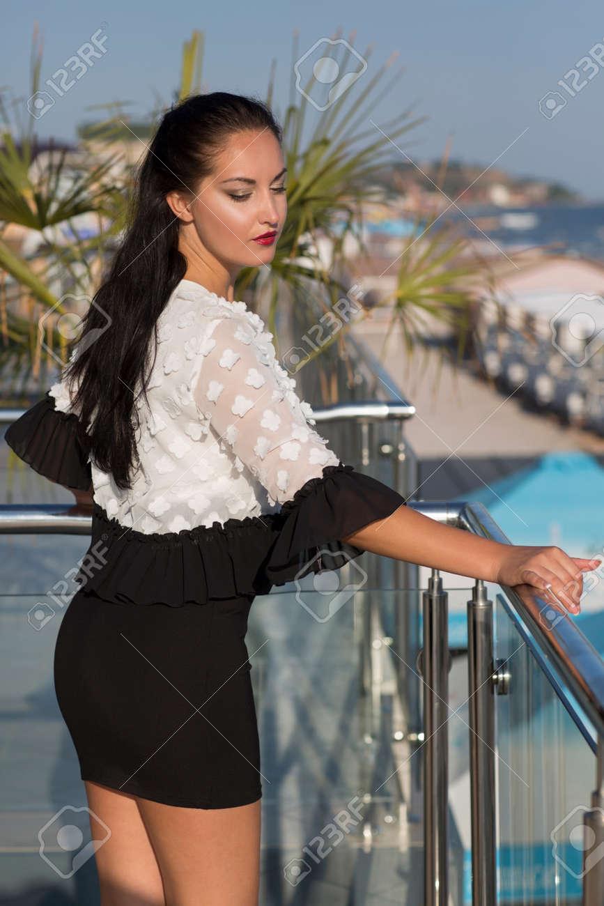d5b7ea99bfd Une Femme Incroyable Dans Une Robe Noire Et Blanche à La Mode Debout Sur Un  Balcon Sur Un Fond D hôtel Lumineux. Une Dame Brune Luxueuse Dans Une  Station ...