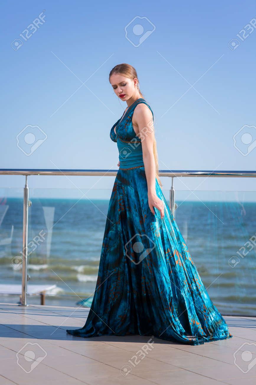 eeae2d4ccdce Una bellissima e giovane donna in un abito turchese è in posa in un balcone  di vetro su uno sfondo di mare. Signora alla moda ed elegante in vestito di  seta ...