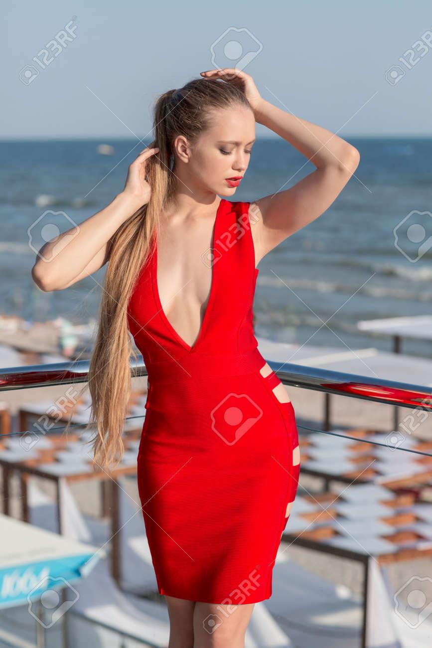 高級ホテルのテラスでポーズかっこいい女。海のそばの長い光の茶色の髪の美しい少女。エレガントな明るい赤ドレスでセクシーな女性。