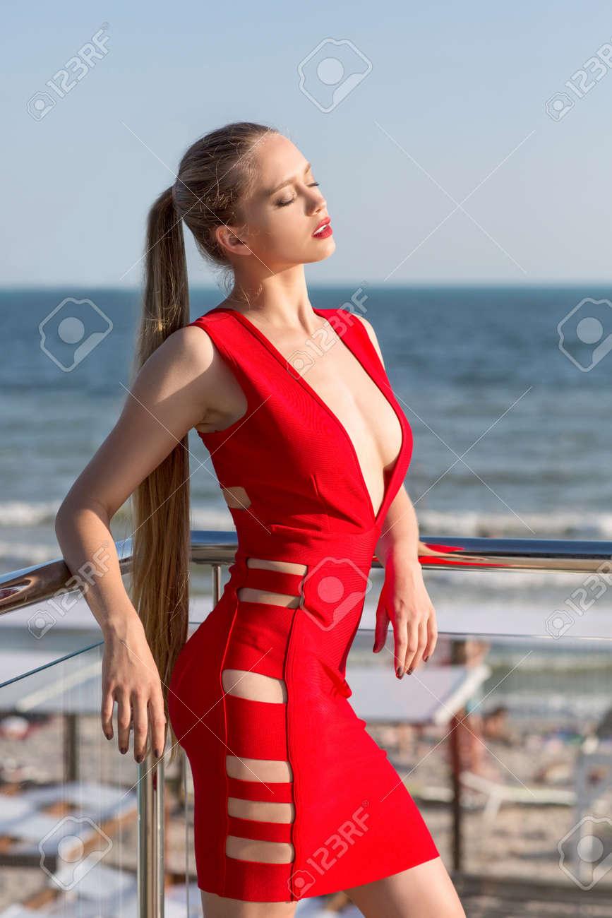 f9be247b143 Une Femme Magnifique Dans Une Robe Rouge Vif Sur Le Fond De La Mer. La Femme  Sexy Et élégante Avec Les Cheveux Réunis Se Pose Près De La Mer.