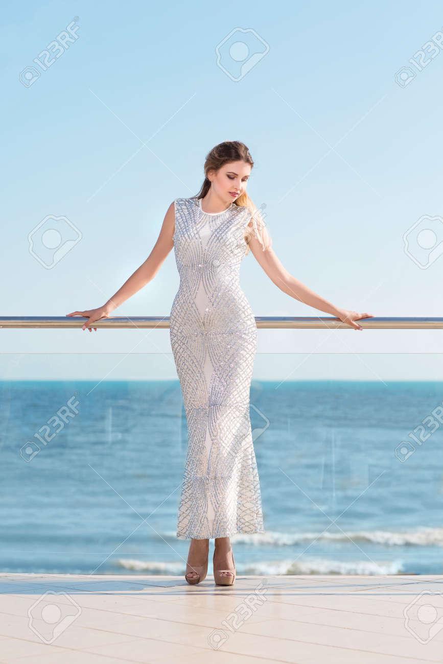 b5ac47dd97 Foto De Cuerpo Entero De Una Mujer Romántica En Un Vestido Blanco Largo. La  Señora Joven Bonita Alta Que Se Relaja En Un Balcón De Cristal Soleado En  Un ...