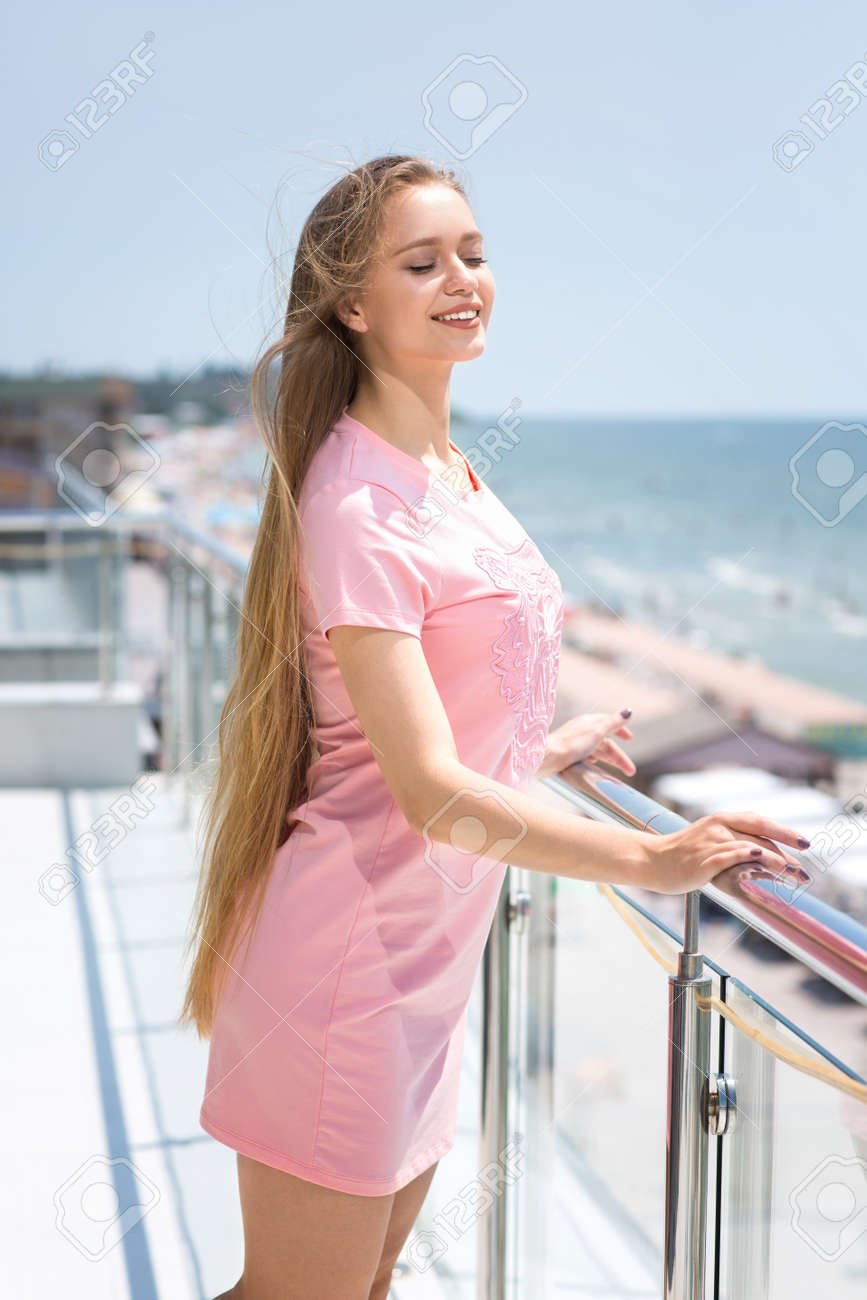 A Charming And Smiling Woman With Light Brown Hair In A Pink Stock