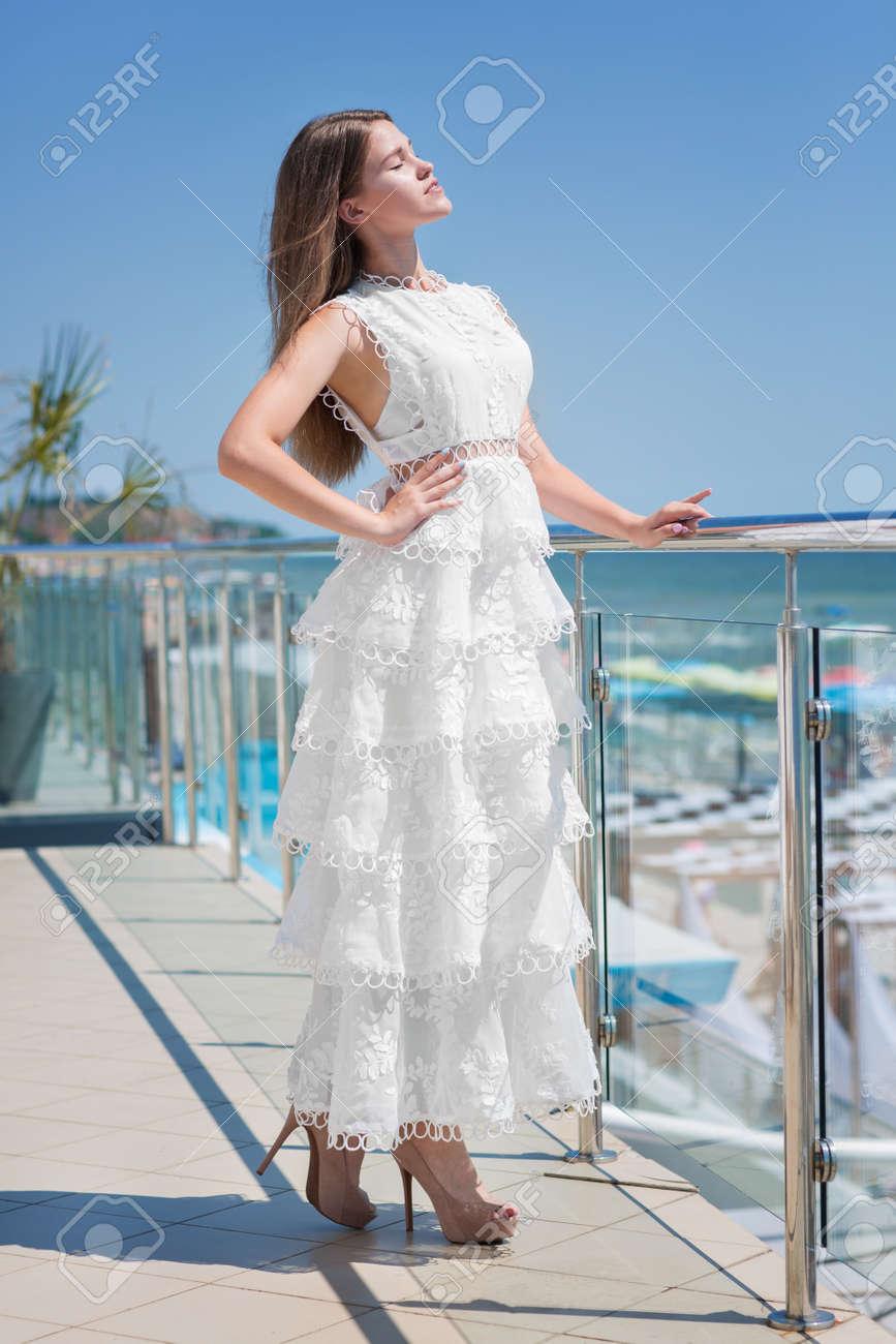 9b1cb6bc95a Une Femelle Magnifique Et Confiante Pose Sur Un Balcon Transparent  Ensoleillé Sur Un Fond De Ciel Bleu. La Femme élégante Aux Cheveux Châtain  Clair Dans Une ...
