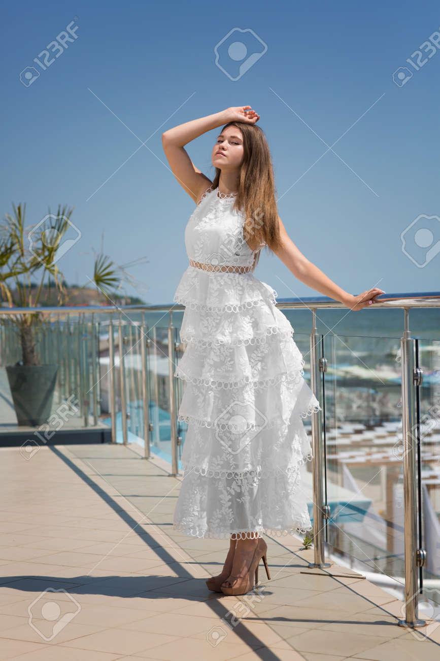 73240a80c232 Una femmina elegante e giovane su una terrazza su una priorità bassa del  mare blu. Una bella ragazza in un abito bianco e lungo con le ruches.