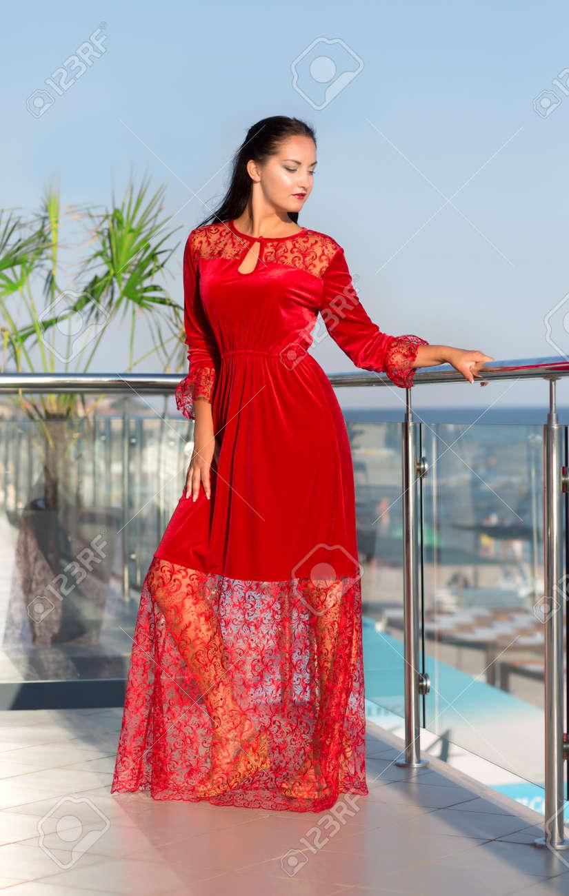 0ccb49b9dbb6 Archivio Fotografico - Una signora in un vestito rosso che propone su una  priorità bassa di soleggiato resort. Una giovane donna elegante su un  balcone di ...
