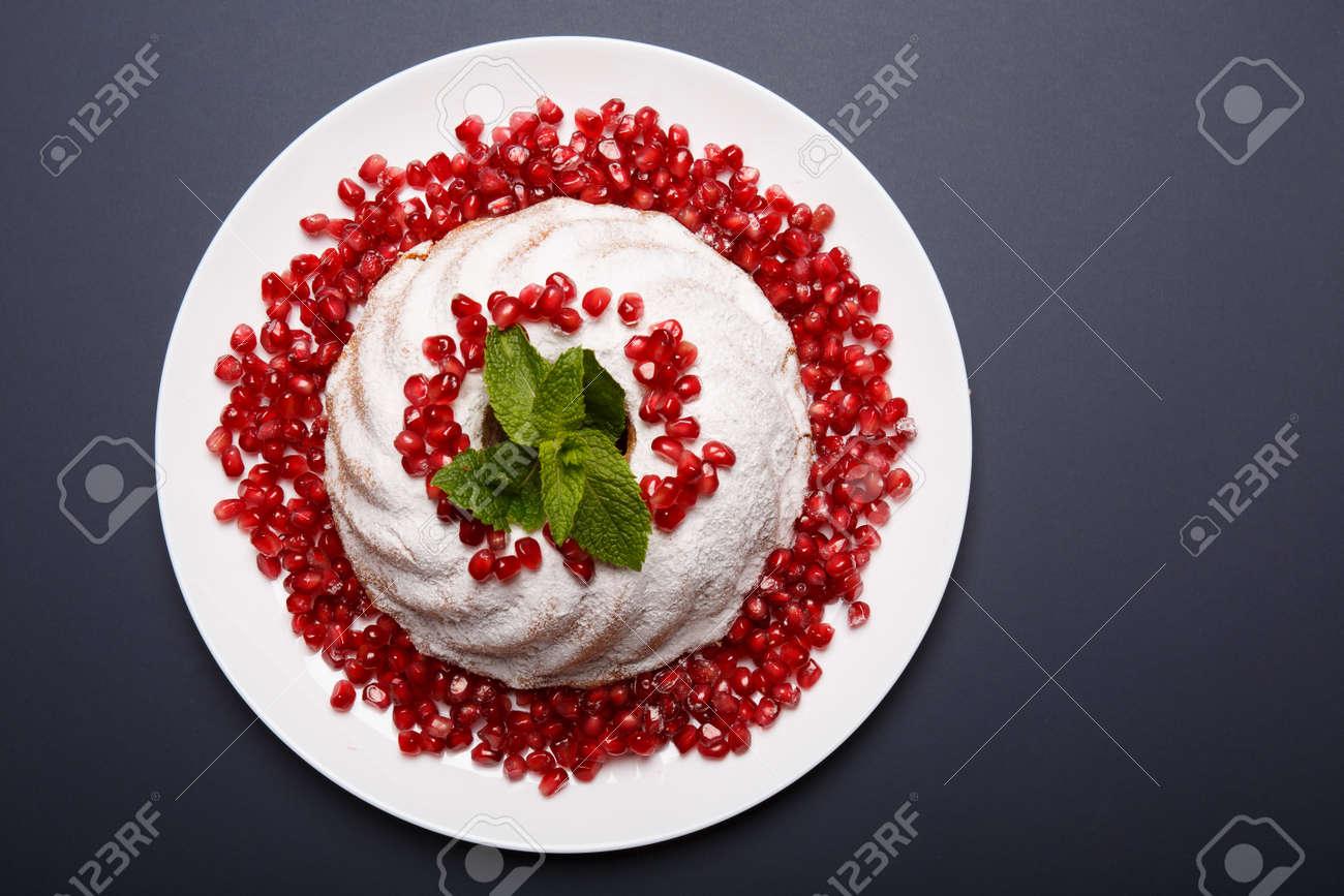 砂糖粉末アイシング、赤ザクロ粒および芳香族のミントの葉と白のマーブル ケーキの平面図です。紫色の背景に自家製ケーキ プレート。クラシックなお菓子のレシピの