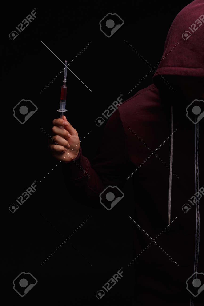 Photo of desperate young drug addict wearing a hood with a syringe