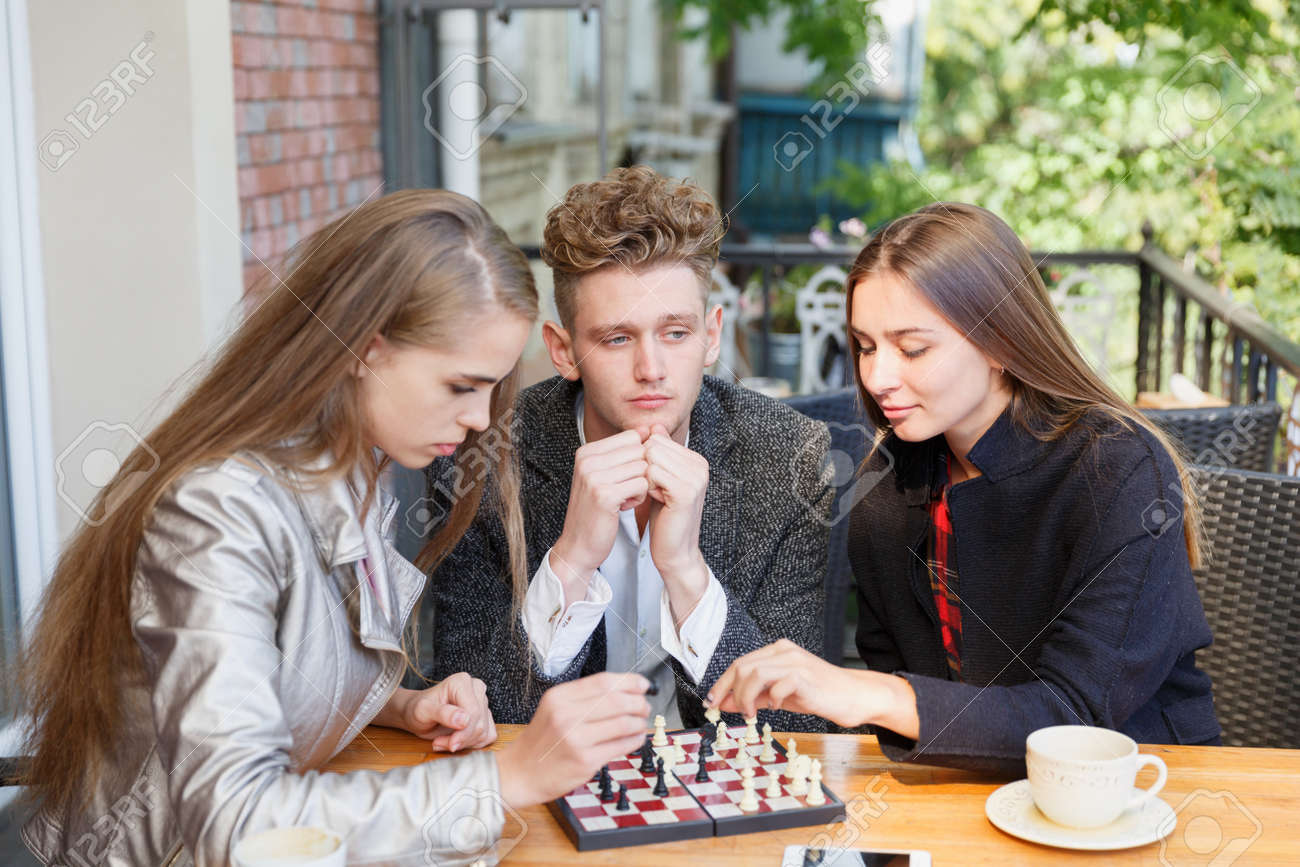 Handsome guy and smart girl friends playing chess on a cafe background