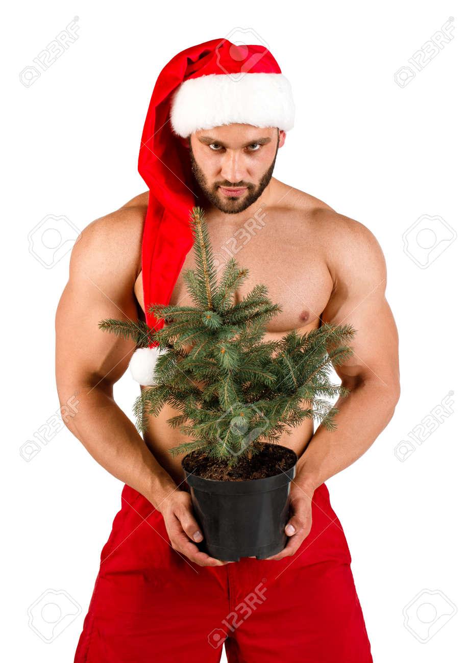 Chico Joven Desnudo Fuerte Vestido Como Santa Claus Con árbol De Navidad En Su Mano Y Sombrero Rojo Aislado En Blanco