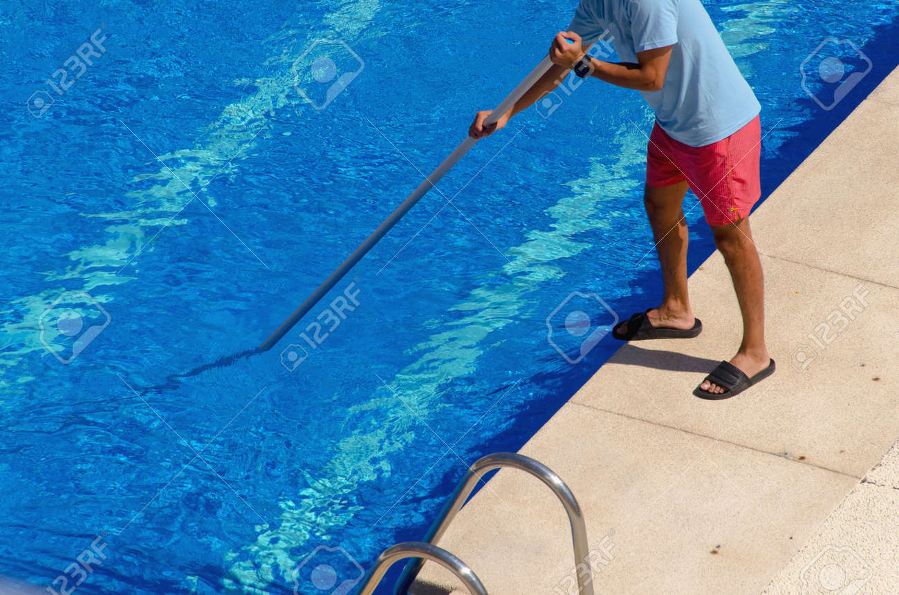 A guy cleaning the swimming pool ground with a vacuum head. Summer..
