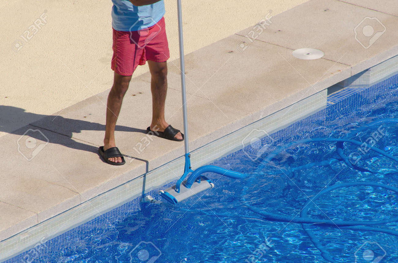 A Man Cleans The Swimming Pool Ground With A Vacuum Head And.. Stock ...