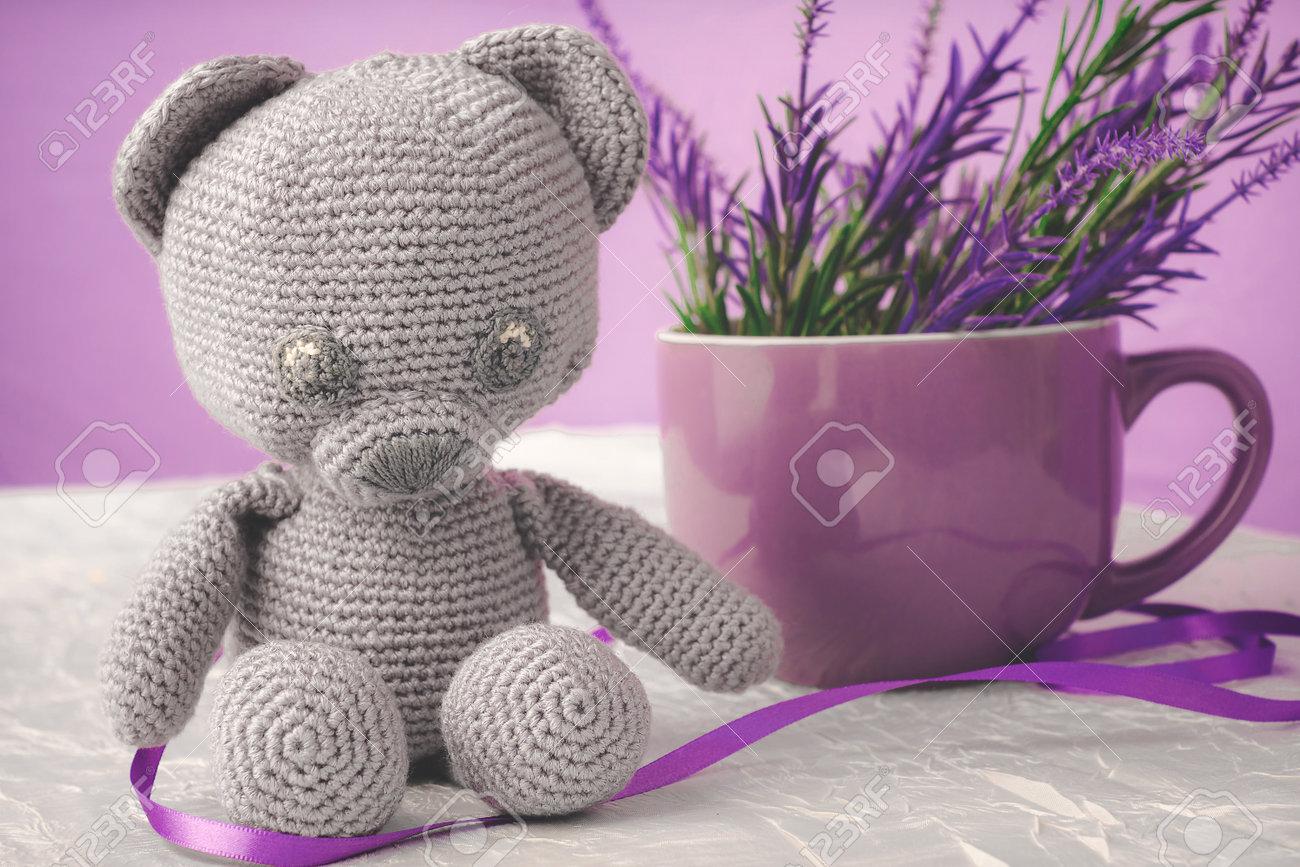 Oso de juguete tejido de estambre, al lado de una taza decorada con lores artificiales - 163787069