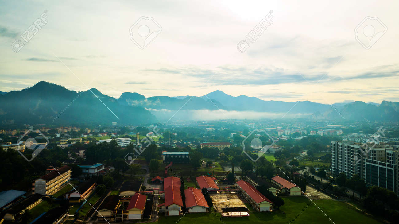 Aerial photography of a mist covered mountain in Ipoh during sunrise with a school in the foreground. - 123744422
